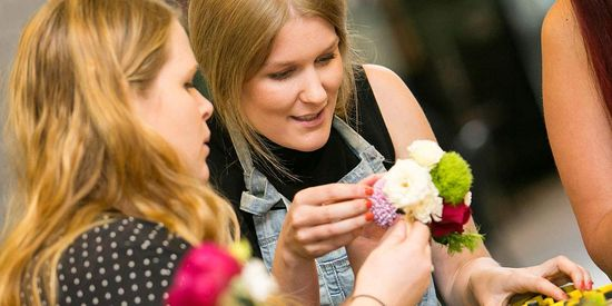 Visitors making flower arrangements at an event held at Collins Square